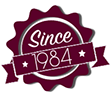 maroon star shaped badge reading since 1984